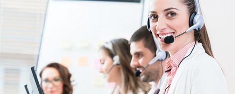 Woman and men working as call center agents giving helpdesk service