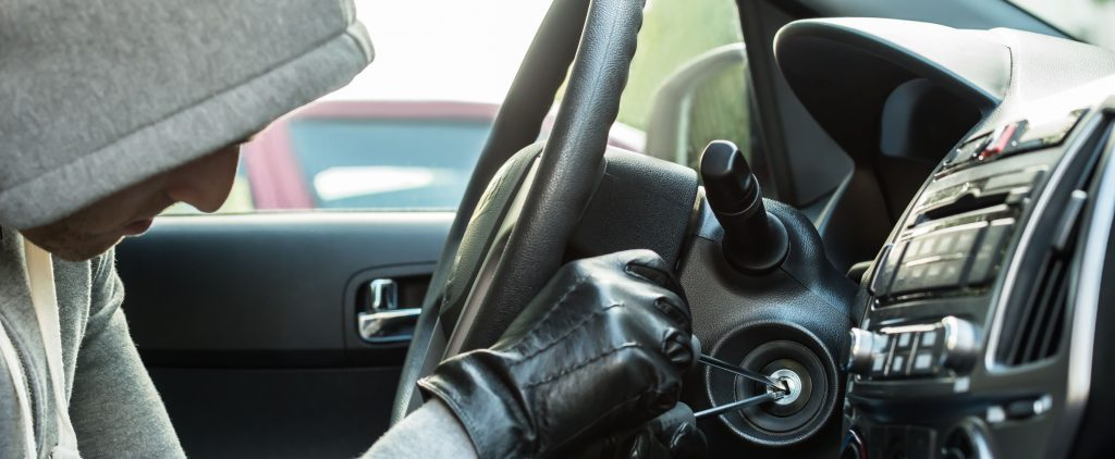 Close-up Of Thief Using Tool To Steal Car